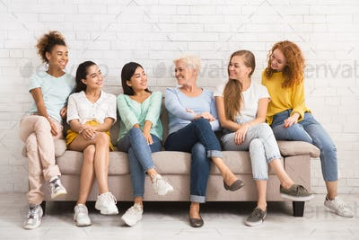 Multiethnic Women Looking At Each Other Sitting On Sofa Indoor