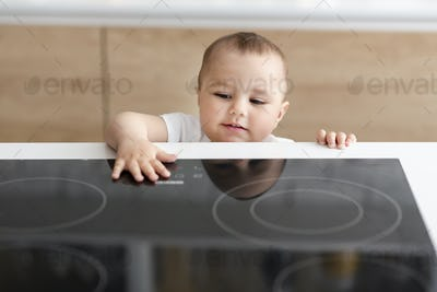 Curious toddler reaching hand to hot electric cooktop