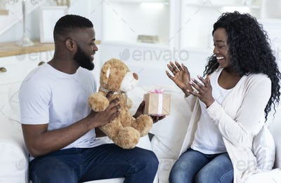 Romantic surprise. Millennial guy giving present to his pleased girlfriend