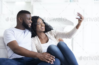 African american couple taking self-photograph to post in social networks