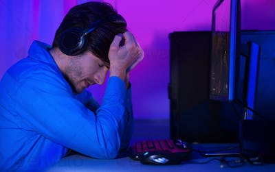 Loss control. Upset gamer in headphones expressing disappointment