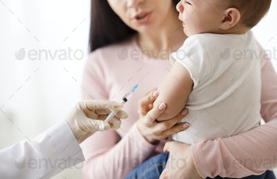 Doctor giving intramuscular injection to little baby