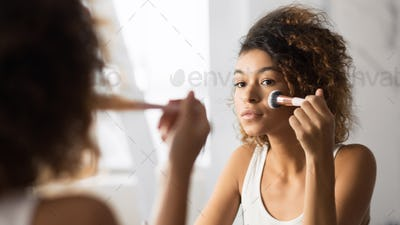 Afro Woman Applying Face Powder With Makeup Brush In Bathroom