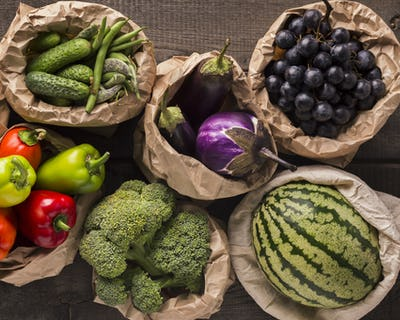 Fresh and eco fruits and vegetables in natural sacks on wood
