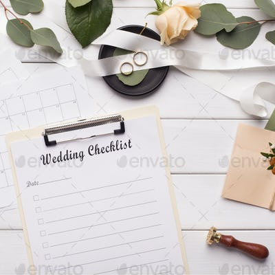 Wedding checklist and accessories on white wooden background