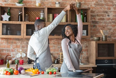 African american couple in love dancing in kitchen