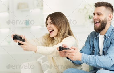 Joyful couple playing online video games by joysticks