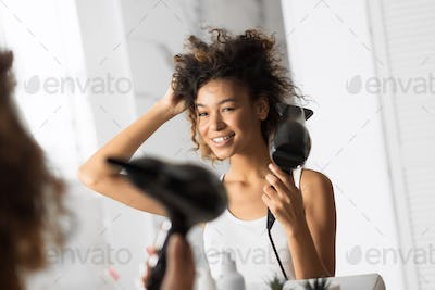 African American Woman Drying Hair With Fan In Bathroom