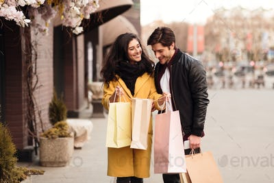 Woman showing man her purchases, guy looking into shopping bag