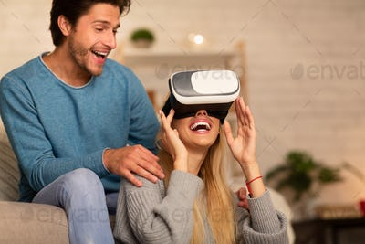 Couple Using Virtual Reality Glasses Playing Videogame At Home