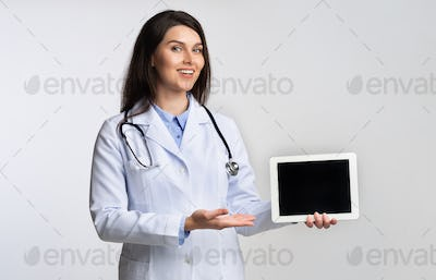 Positive Doctor Using Tablet Giving A Presentation On White Background