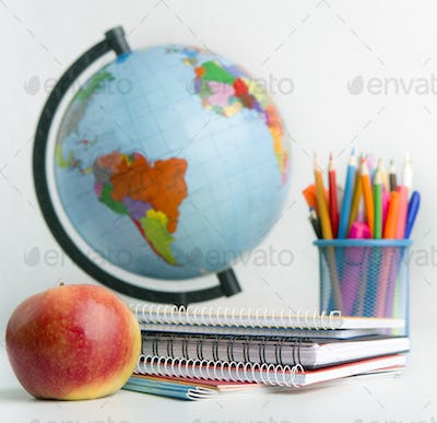 Close up of world globe and school stationery on white