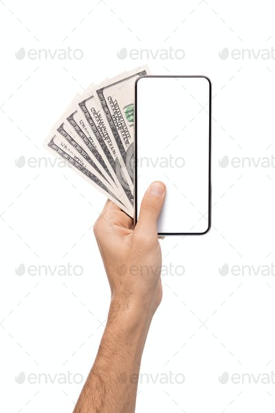 Male hand holding blank cellphone and dollar banknotes