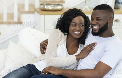 Happy black couple sitting on couch at home, cuddling