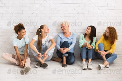 Multiethnic Women Smiling At Each Other Sitting On Floor Indoor