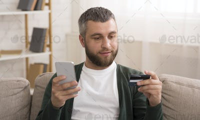 Man holding credit card, making online shopping with cellphone