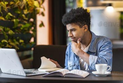 Hard-working student making homework, using laptop at cafe