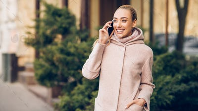 Happy smiling woman talking on cellphone outdoors in city