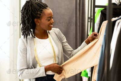 Smiling Dressmaker Looking At New Clothing Collection In Showroom