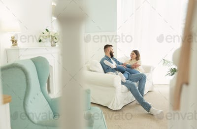Love story. Happy couple sitting on sofa, in light interior room