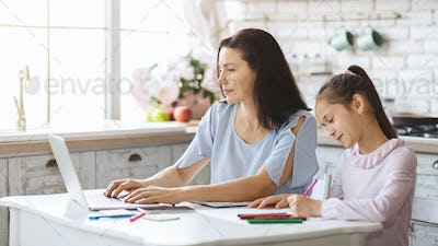 Woman working on laptop while her daughter doing homework
