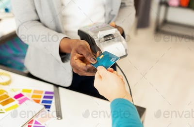 Shop Assistant Conducting Credit Card Payment In Fashion Atelier, Closeup
