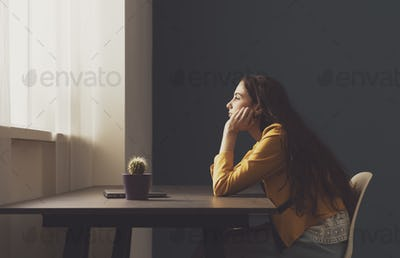 Sad lonely young woman sitting at home
