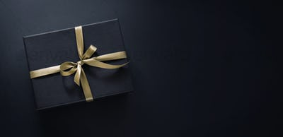 Gift wrapped in dark paper on dark background