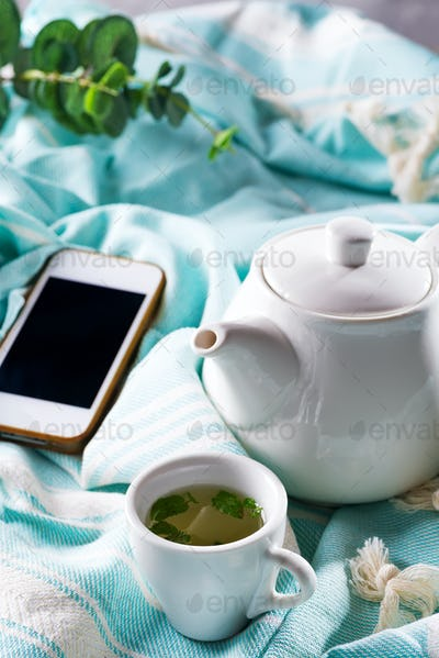 White cup and teapot with blue plaid and phone on a bed . Breakfast in bed. Sweet home
