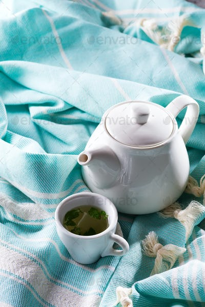 White cup and teapot with blue plaid on a bed . Breakfast in bed. Sweet home