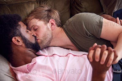 Loving Male Gay Couple Relaxing Lying On Sofa At Home Hugging And Kissing