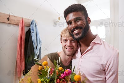 Portrait Of Man Giving Gay Partner Bunch Of Flowers In Hallway At Home