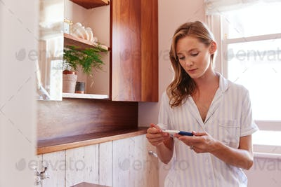 Woman Looking At Positive Result Pregnancy Test In Bathroom