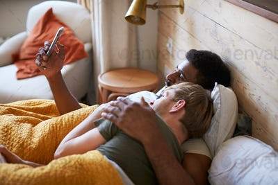Male Gay Couple Lying In Bed At Home Checking Mobile Phones Together