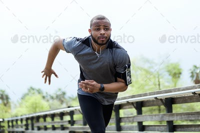 Fit and sporty young man running in the city.
