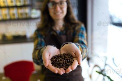 Beautiful young saleswoman holding coffee grains in organic shop