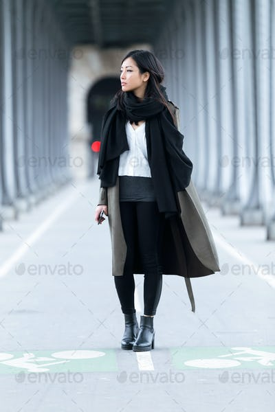 Pretty asian young woman looking sideways in the street.