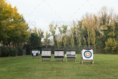 Outdoor archery targets on grass field surrounded by forest.