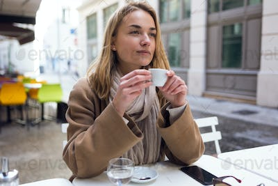Pretty young woman looking sideways while drinking cup of coffee