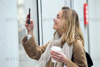 Beautiful young woman making photos of a shop window with mobile