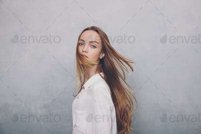 Fashion teenager girl standing against blue textured grunge wall background