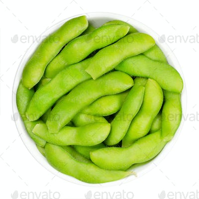 Edamame, green soybeans in the pod, in white bowl