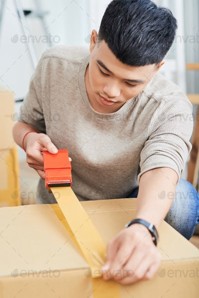 Asian man sealing carton box