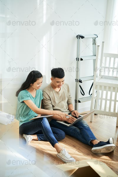 Young couple browsing laptop during relocation