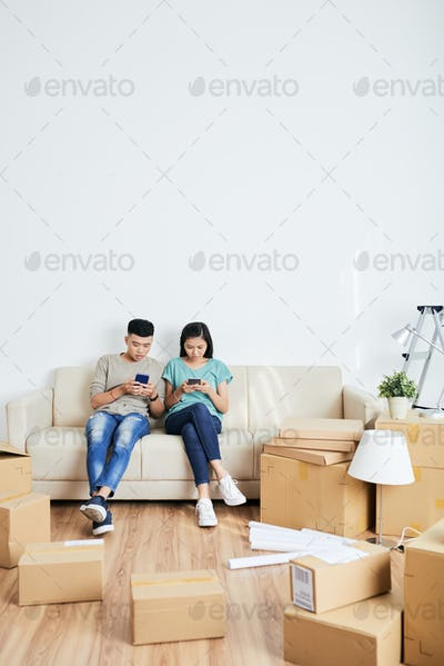 Asian couple using smartphones in new apartment