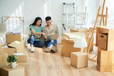 Asian couple using gadgets among boxes