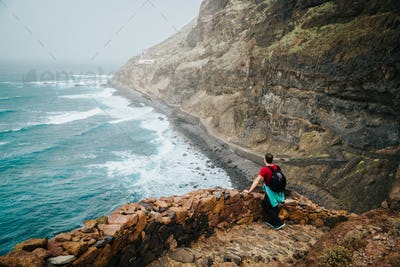 Men hiker with backpack on the scenic coastal road. The route leads along huge volcanic rock cliffs