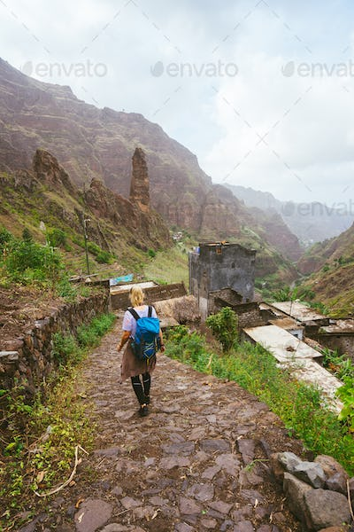 Girl with backpack walking down along the trekking route to verdant Xo-Xo valley. Mountain peaks and