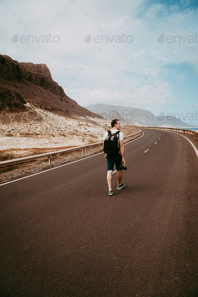 Traveler walks in the center of an epic winding road. Huge volcanic mountains in the distance behind