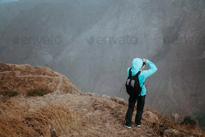 Man in high altitude rocky mountain landscape in front of a deep ravine. Trekking trail on Santo